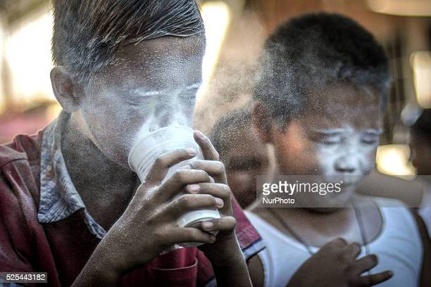 Children blow into cups filled with flour during parlour games as part of the feast day of Saint Rita of Cascia in Paranaque Metro Manila Philippines...