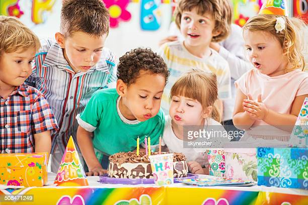 children blowing birthday candles. - happy birthday stock pictures, royalty-free photos & images
