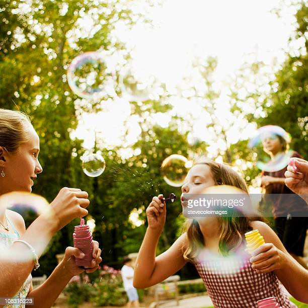 Children Blowing Bubbles in Park