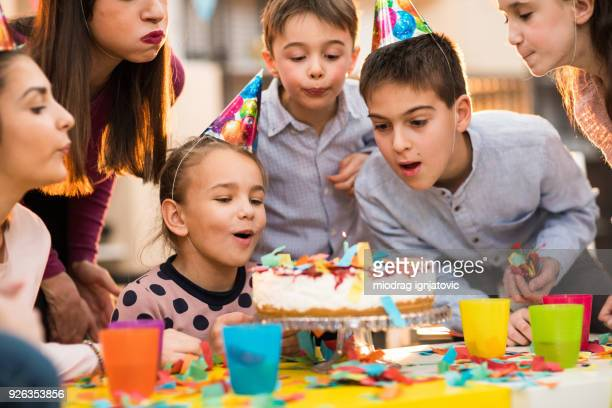 Children Blowing candles on a Birthday party