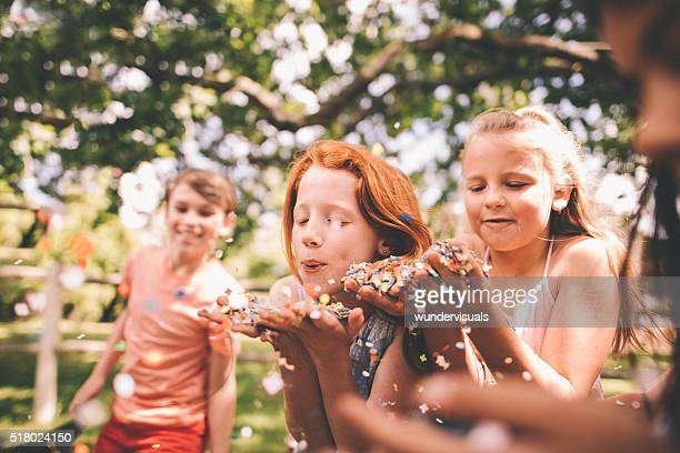 Children blowing colourful confetti in a sunny park