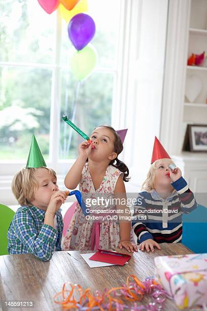 Children blowing party horn blowers