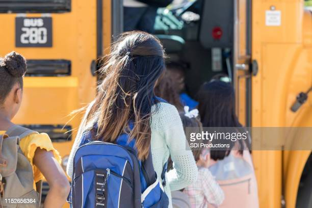 children board a school bus in a line - obscured face stock pictures, royalty-free photos & images