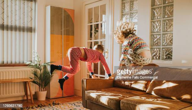 children bouncing on a brown leather sofa in a sunny domestic room - childhood stock pictures, royalty-free photos & images