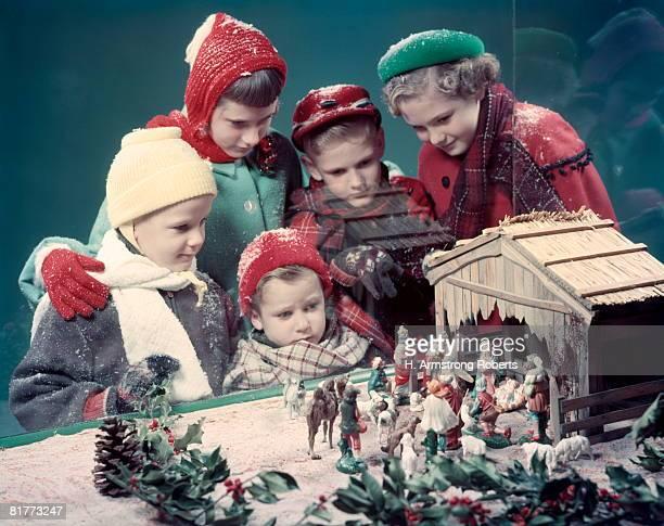 5 Children Boys Girls Looking In Window At Nativity Scene Creche Display All Kids Wear Gloves Hats Coats Snow.