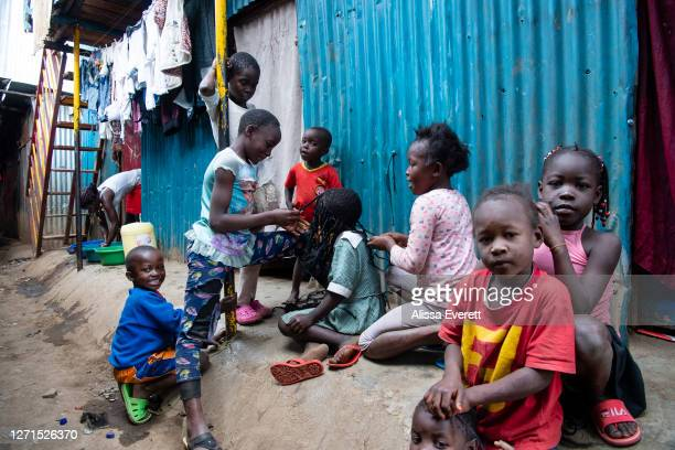 Children braid hair and play in the streets on July 9, 2020 in Nairobi, Kenya. Since school has been out, kids fill the streets of Mathare informal...