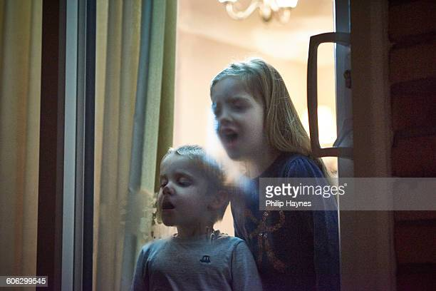children breathing on cold window