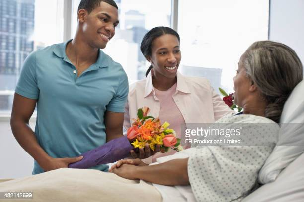 children bringing mother flowers in hospital - patients brothers stock pictures, royalty-free photos & images