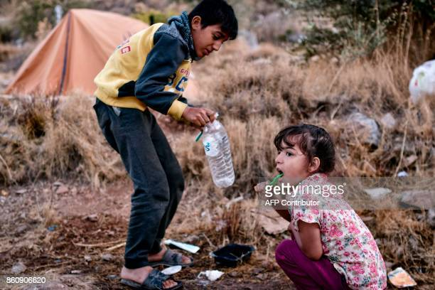 Children brush their teeth at a makeshift tent camp near the overcrowded hotspot on the Greek eastern Aegean islands of Samos on October 13 2017 More...