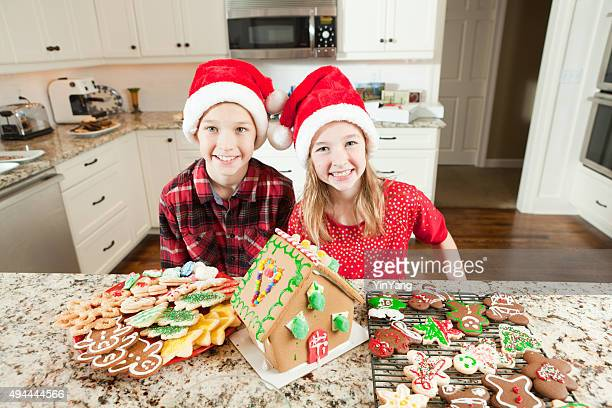 Children Building and Decorating Christmas Ginerbread House Cookies