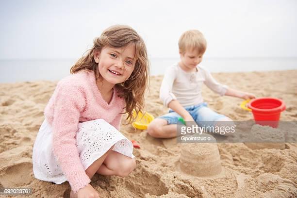 Children building sand castle on beach