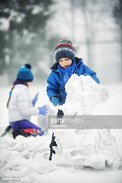 Children building snowmen on a winter day