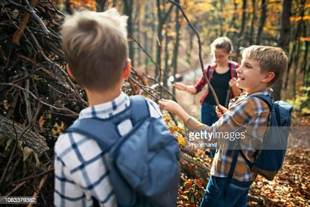 children building stick shelter in autumn forest - shack stock pictures, royalty-free photos & images
