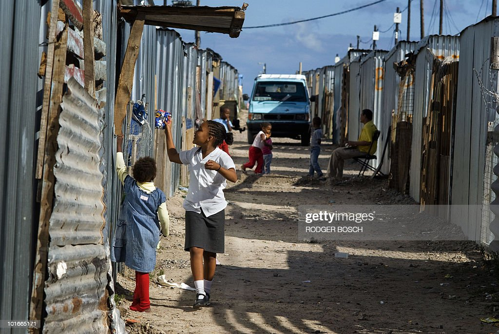 Children buy snacks from an informal shop in Blikkiesdorp ('Tin Can Town' in Afrikaans), a settlement of corrugated iron houses, on April 20, 2010 about 25Km East of Cape Town, South Africa. South Africa has poured billions into hosting Africa's first football World Cup with new stadiums, transport systems and a beefed up police force. But while children gleefully undergo football training on a sandy patch near a busy road, there is little sign in Blikkiesdorp of the World Cup kick-off on June 11.