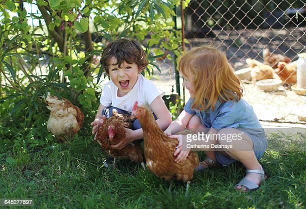 2 children caressing chicken