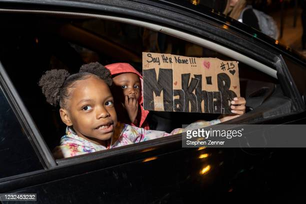 Children carry a sign at a Black Lives Matter protest as it makes it's way through downtown in response to the police shooting of MaKhia Bryant on...