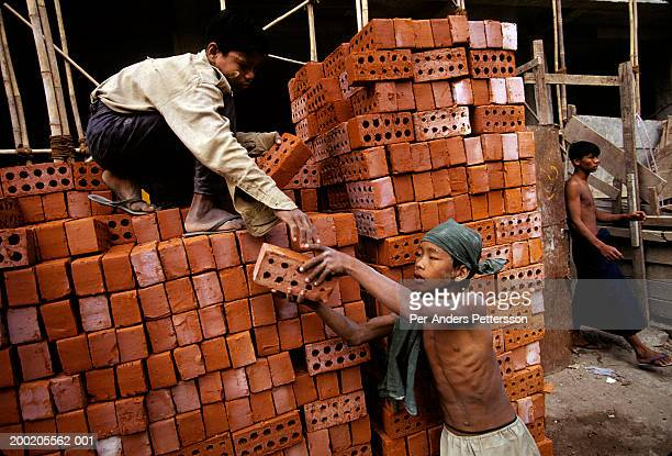Children carry bricks at a construction site in Rangon, Burma