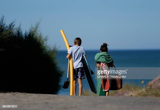 Children carry items as they walk to the beach on August 23 2016 in Varaville northwestern France