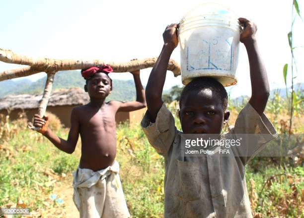 Children carry logs and buckets on November 07 2009 in Bauchi Nigeria