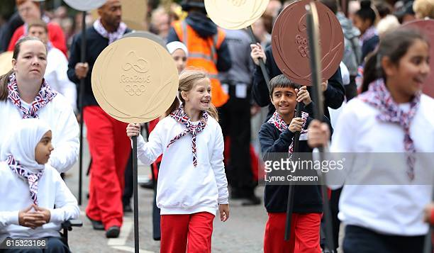 Children carry medals during a Rio 2016 Victory Parade for the British Olympic and Paralympic teams on October 17 2016 in Manchester England