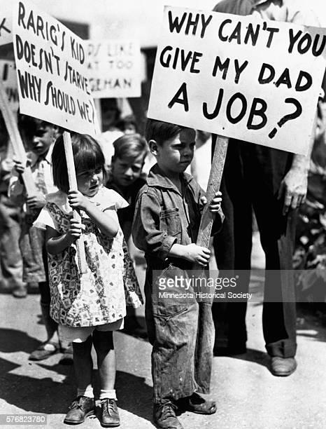 Children carry picket signs at a demonstration for the Workers Alliance during the Great Depression.