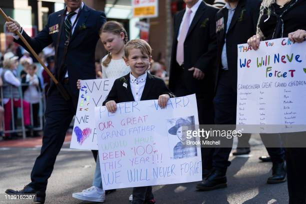 Children carry signs for lost loved ones during the ANZAC Day March on April 25 2019 in Sydney Australia Australians commemorating 104 years since...