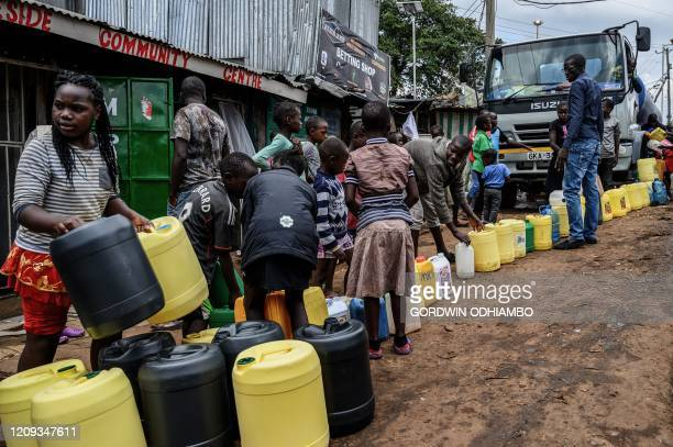Children carry their jerrycans to fill them with free water distributed by the Kenyan government at Kibera slum in Nairobi Kenya on April 7 2020...