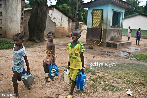 Children carry water containers after fetching water from a tap stand in Bangui The water costs 15 CFA per gallon of water and a family of four or...