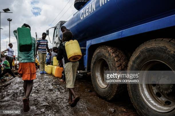 Children carry water jerrycans to fetch free water distributed by the Kenyan government at Kibera slum in Nairobi Kenya on April 7 2020 President...