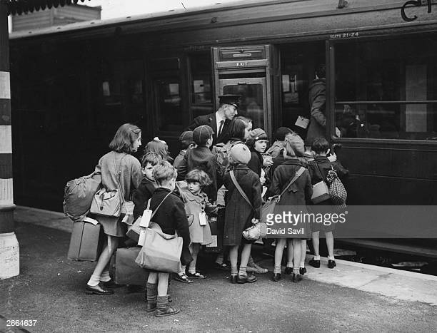Children carrying bags and suitcases board a train which will take them out of wartime London to the safety of the countryside In view of...