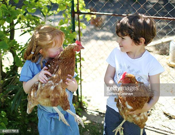 2 children carrying chickens