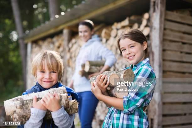 Children carrying firewood outdoors