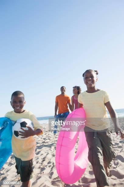 Children carrying inner tubes on beach