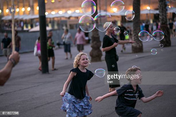 Children Catching Bubbles Joyfully Outdoor
