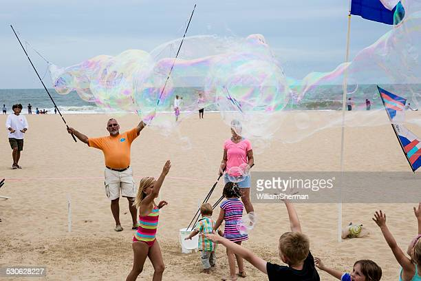 children catching large bubbles - ocean city maryland stock pictures, royalty-free photos & images