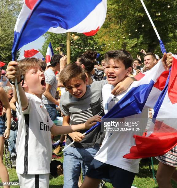 Children celebrate after France scored the opening goal as they watch on a giant screen the Russia 2018 World Cup round of 16 football match between...