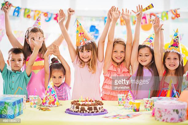 Children celebrating at birthday party with arms raised.