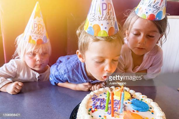 children celebrating birthday blowing a birthday cake candles - birthday cake stock pictures, royalty-free photos & images