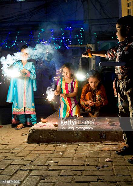 children celebrating diwali - diwali celebration stock photos and pictures
