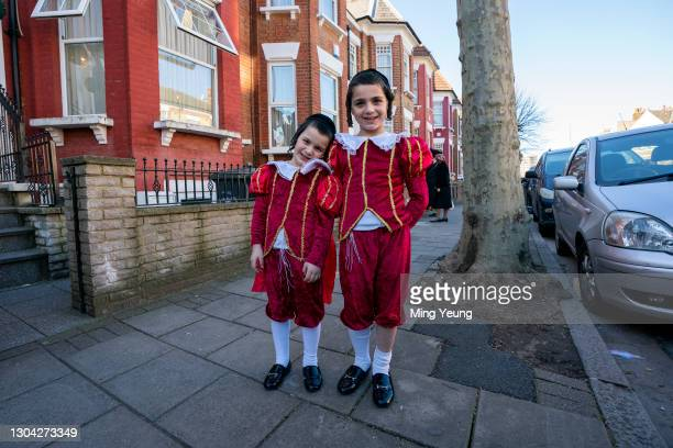 Children celebrating Purim stand in front of their house waiting for guests during Purim on February 26, 2021 in London, England. Last year's Purim...