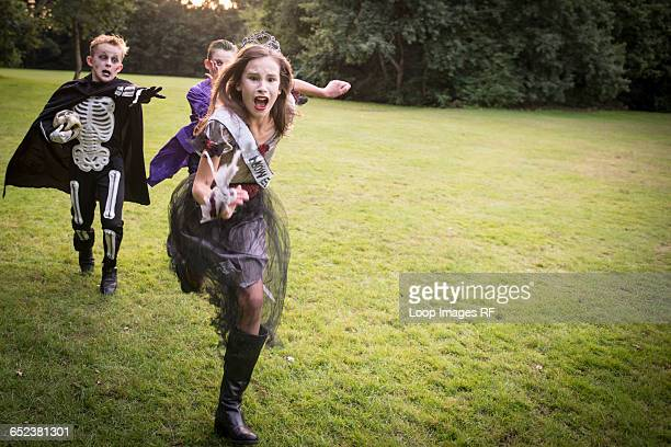 children chase a girl dressed as a zombie prom queen for halloween night - zombie girl stock photos and pictures
