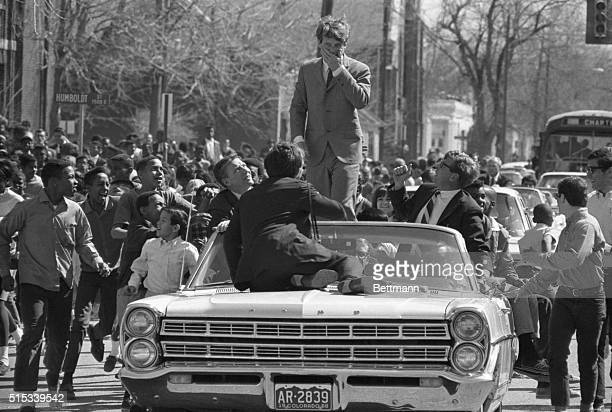 Children chase the car of Senator Robert F Kennedy during a campaign visit to Denver