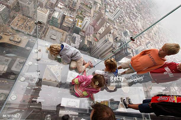Children check out the view from the Ledge a new glass cube that juts out from the 103rd floor Skydeck of the Sears Tower during a media preview July...