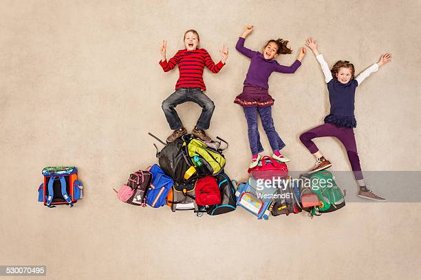 Children cheering on pile of school bags