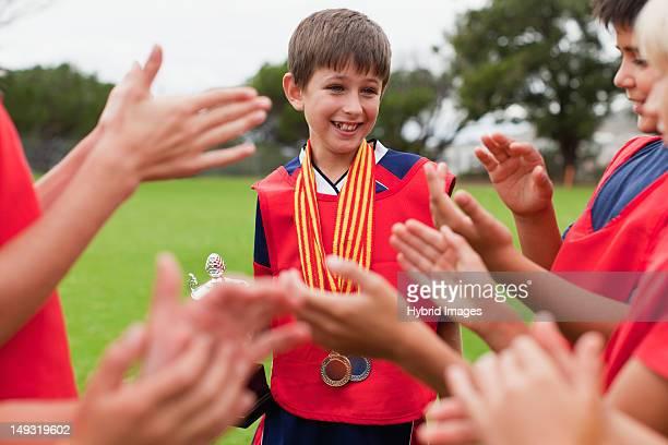 Children cheering teammate with trophy