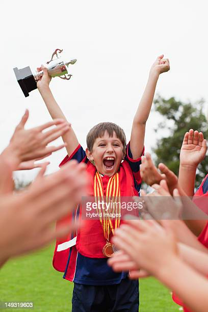 children cheering teammate with trophy - turnover sport stock photos and pictures