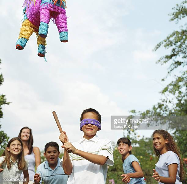Children cheering while boy (8-11) wearing blindfold hits pinata