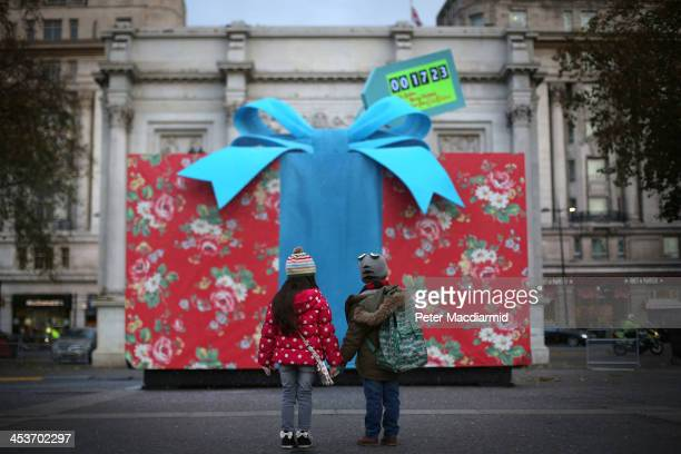 Children Chloe and Michael look upon a giant Christmas present covered in iconic Cath Kidston print at Marble Arch to celebrate the opening of the...