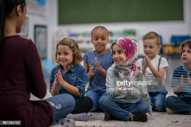 children clapping to a song - refugee stock pictures, royalty-free photos & images