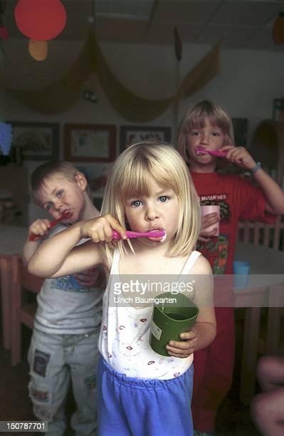 Children cleaning their teeth inside a day nursery in Bonn